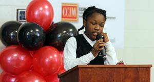 D.H. Stanton Elementary School student in uniform speaking at podium at the event